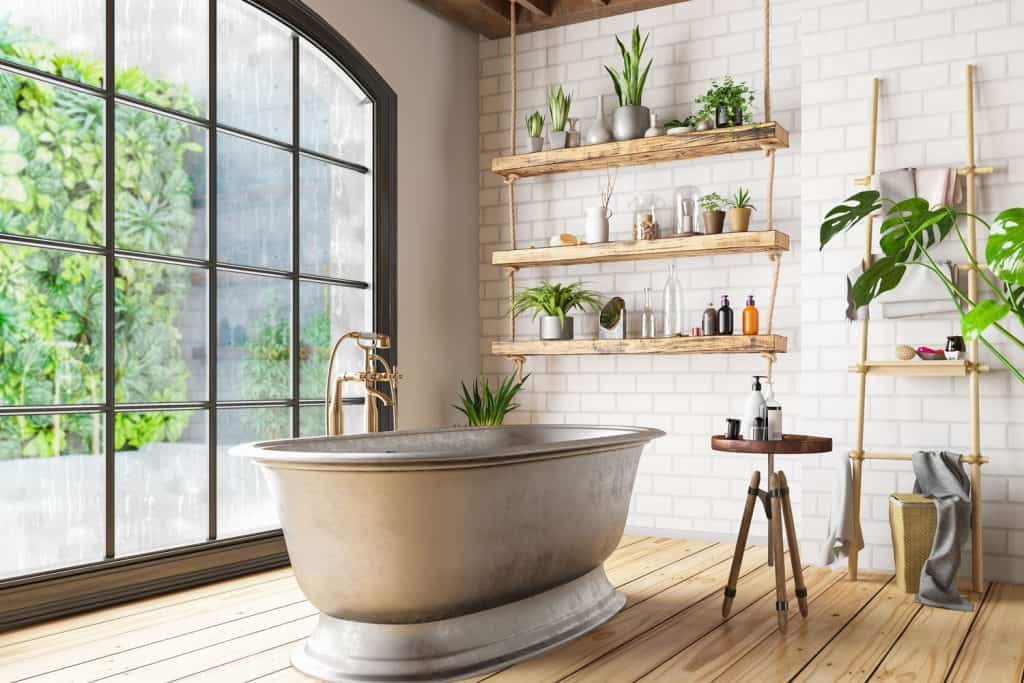A gorgeous eco themed spacious bathroom with indoor plant, huge window, and a wooden flooring