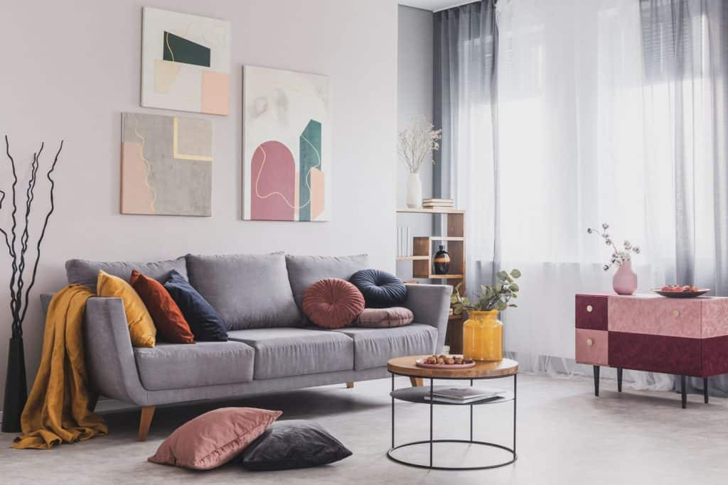 A gorgeous retro themed living room with a grey sofa with different colored throw pillows and a matching gray curtain