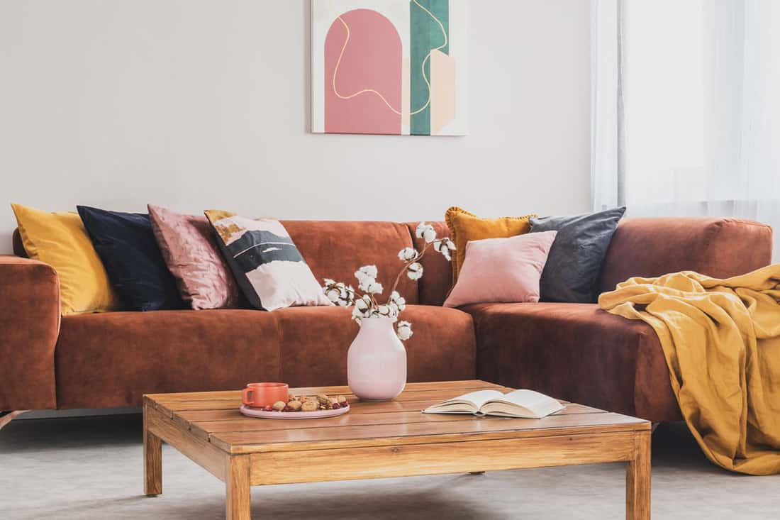 Brown sofa with colored pillows on the corner and an unfolded blanket
