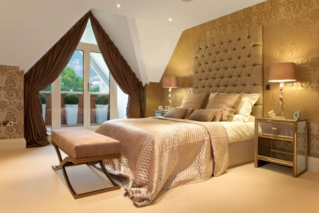 A gold themed bedroom with gold beddings, gold foam header wall and golden floral pattern wall