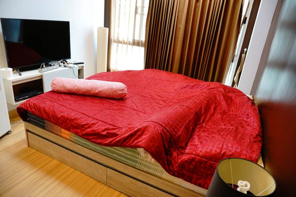 A small hotel bedroom with brown curtains and red beddings