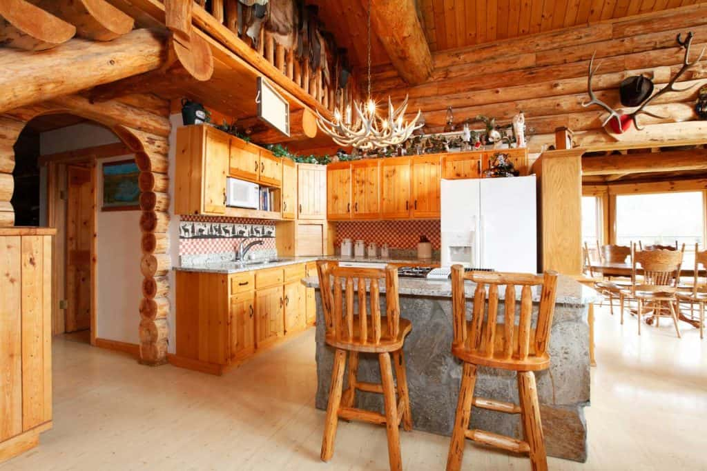 Bright kitchen room with rock counter cabinet, rustic counter stools, horn chandelier in a log cabin chalet
