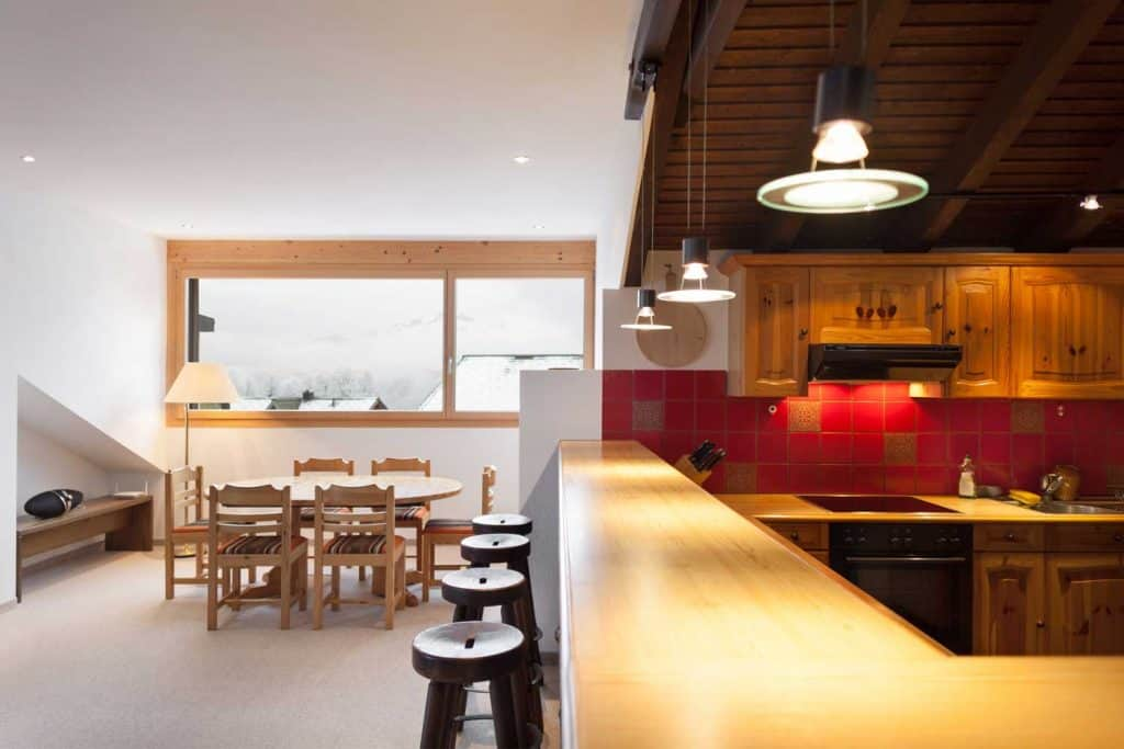 Dark Rustic kitchen with bar stools and a bright dining area in a comfortable chalet