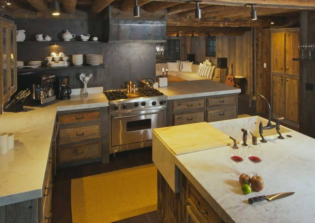 Fully-equipped rustic log cabin kitchen with dark stone walls