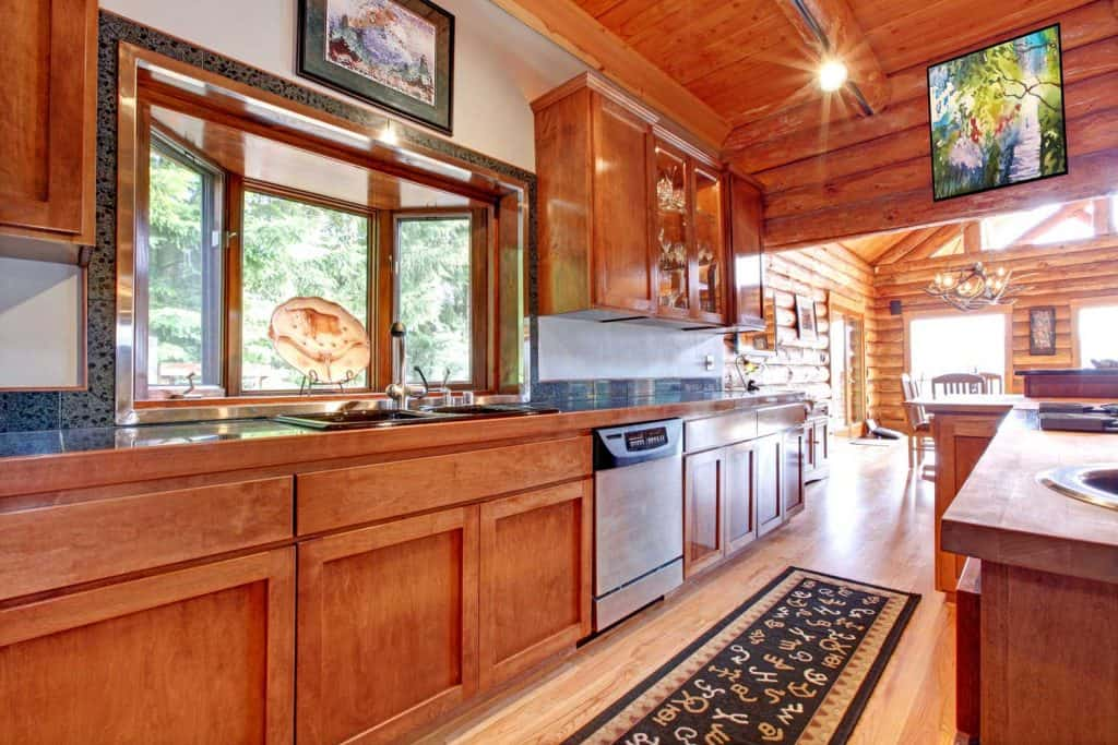 Large kitchen log cabin house interior with wooden cabinets and ceiling