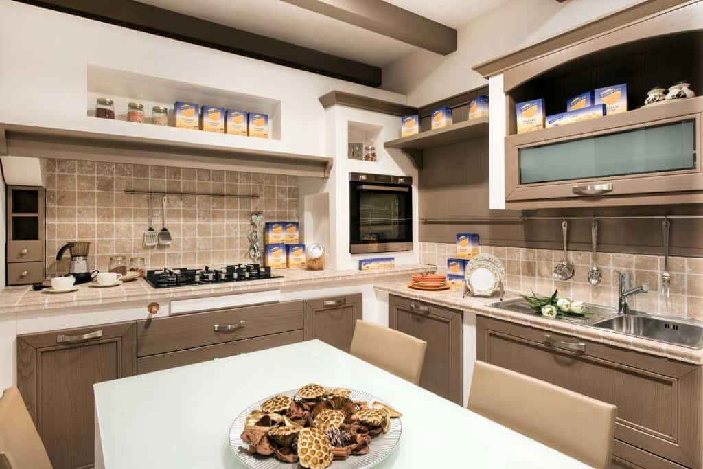Modern rustic kitchen complete with cooking supplies, built-in cabinets, tiled splash back, fitted appliances, and center table