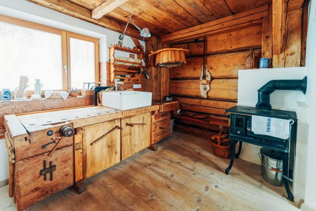 Gorgeous primitive farmhouse kitchen with bold wood cabinets and an iron furnace
