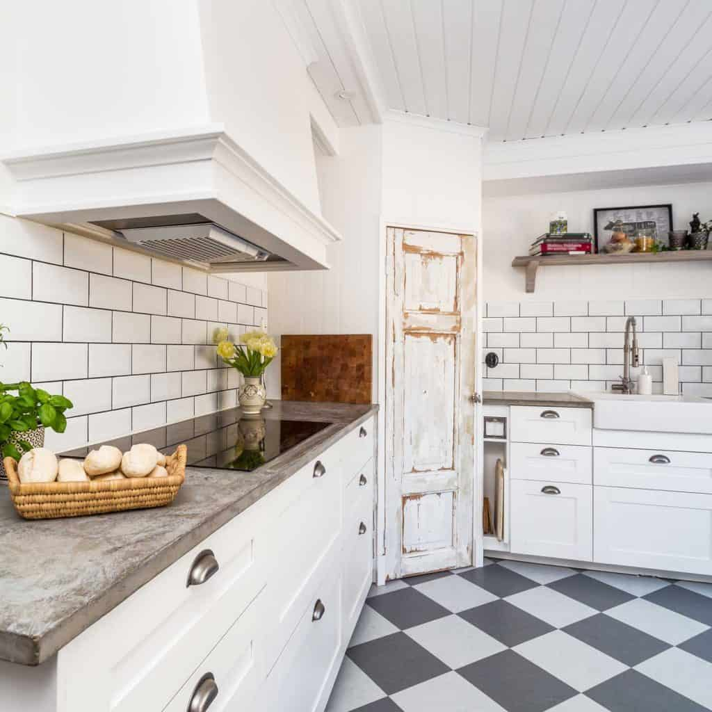 Stone kitchen countertop and whitewashed rough primitive door in Nordic-rustic kitchen