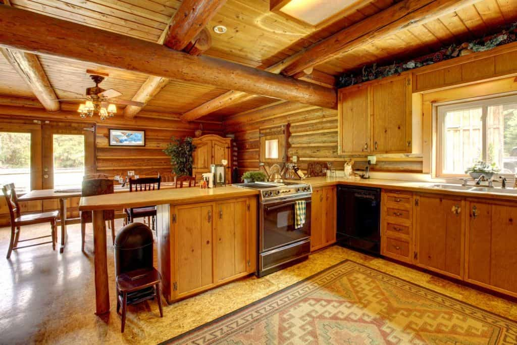 Wood cabin rustic kitchen interior with oak beams and stone flooring