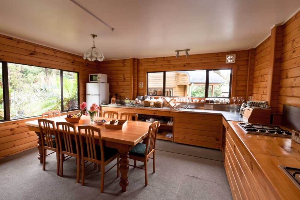 Wood-dominated rustic kitchen with large dining table