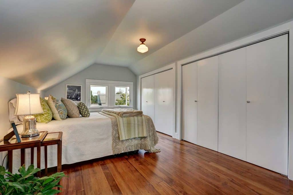 Attic bedroom interior with vaulted ceiling and hardwood floor