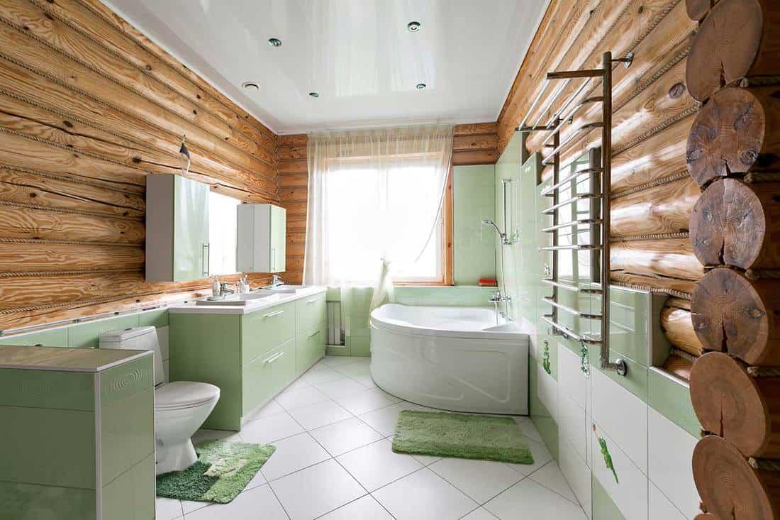 Bathroom in a rustic log cabin with beautiful modern green interior