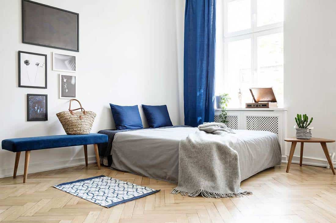 Bed with dark blue pillows and grey duvet and blanket next to window