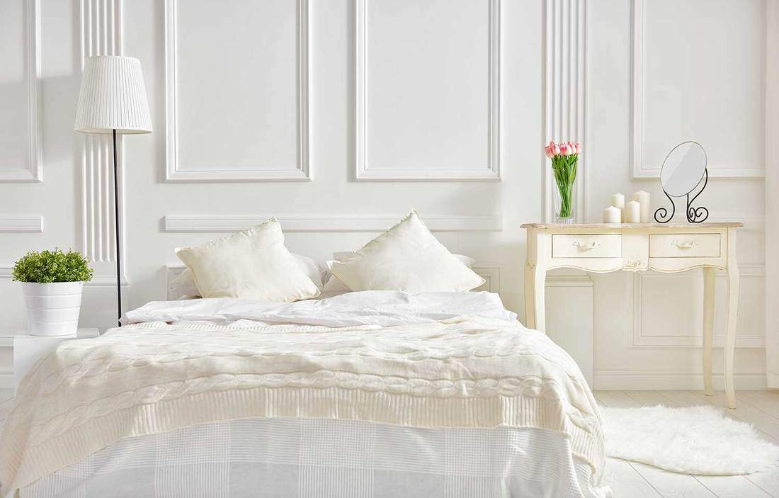 Bedroom in soft light colors. big comfortable double bed in elegant classic bedroom