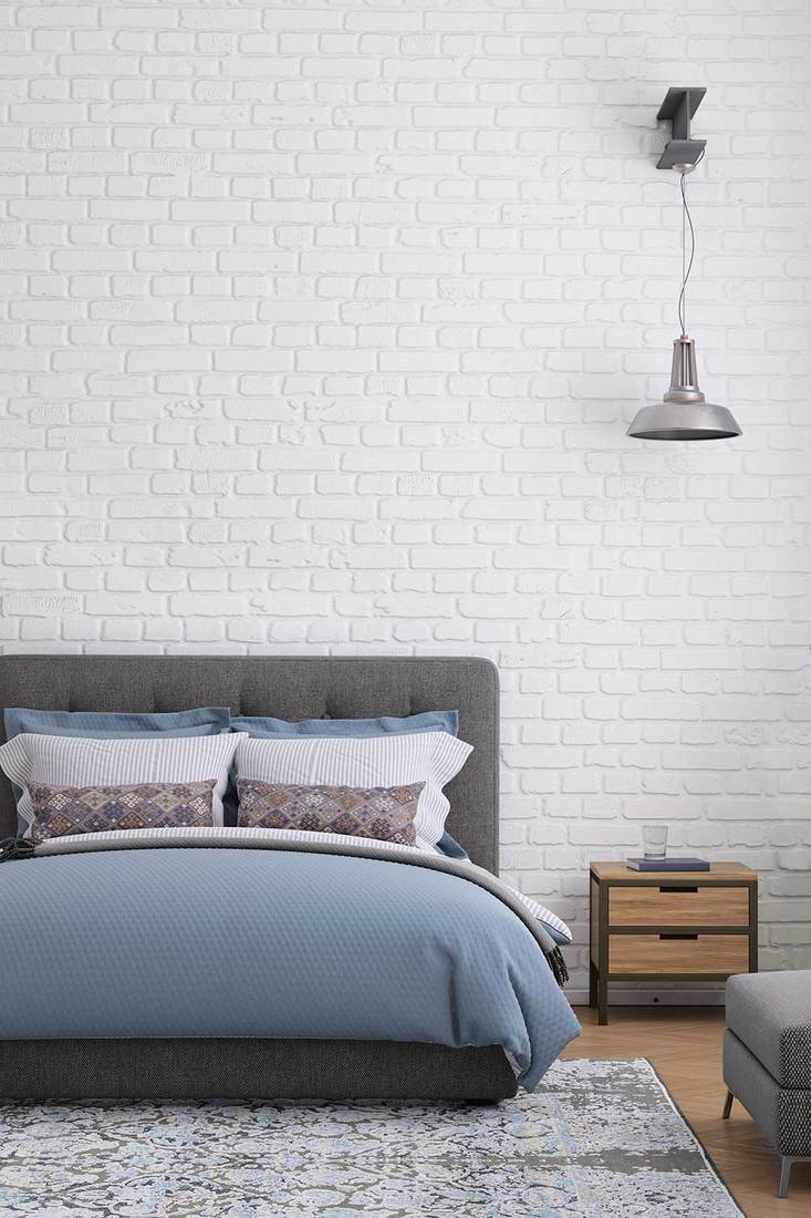 Bedroom with brick wall and hanging lamp