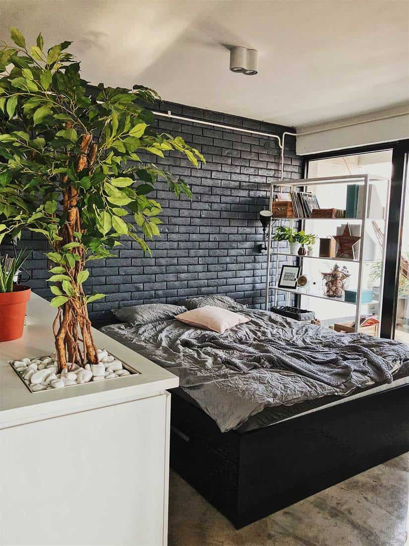 Bedroom with grey brick wall and house plant interior