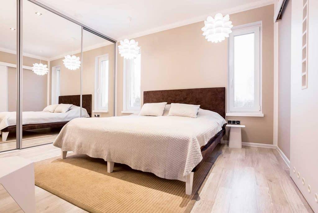 Beige bedroom with mirror wardrobe