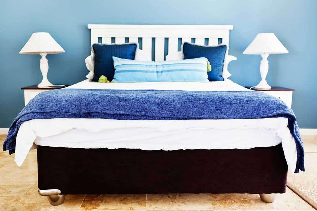 Blue bed in between lamps