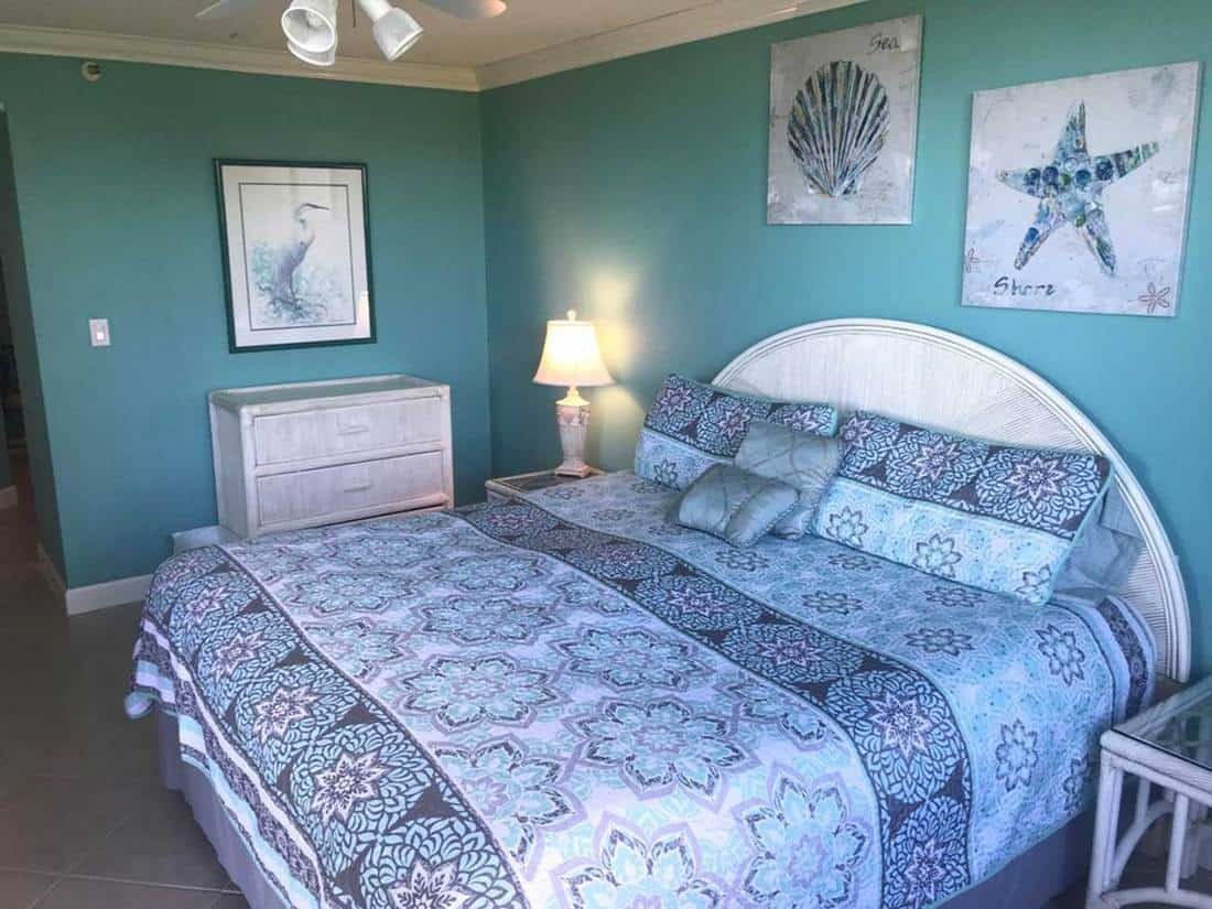Blue bedroom with beach-themed artworks