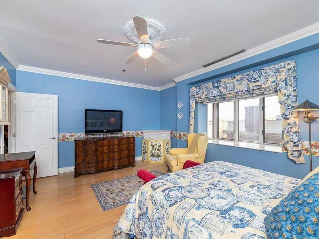 Blue bedroom with wooden interior, yellow sofa chair and tv