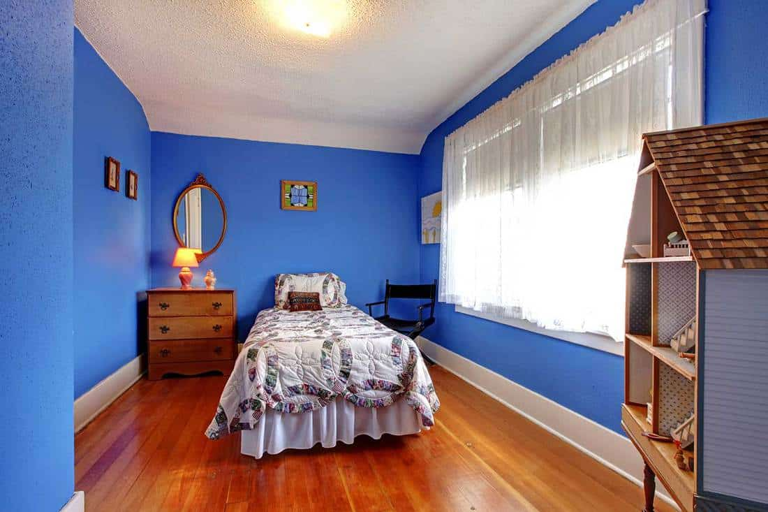 Bright blue kids bedroom in old English style with cherry hardwood floor and doll house