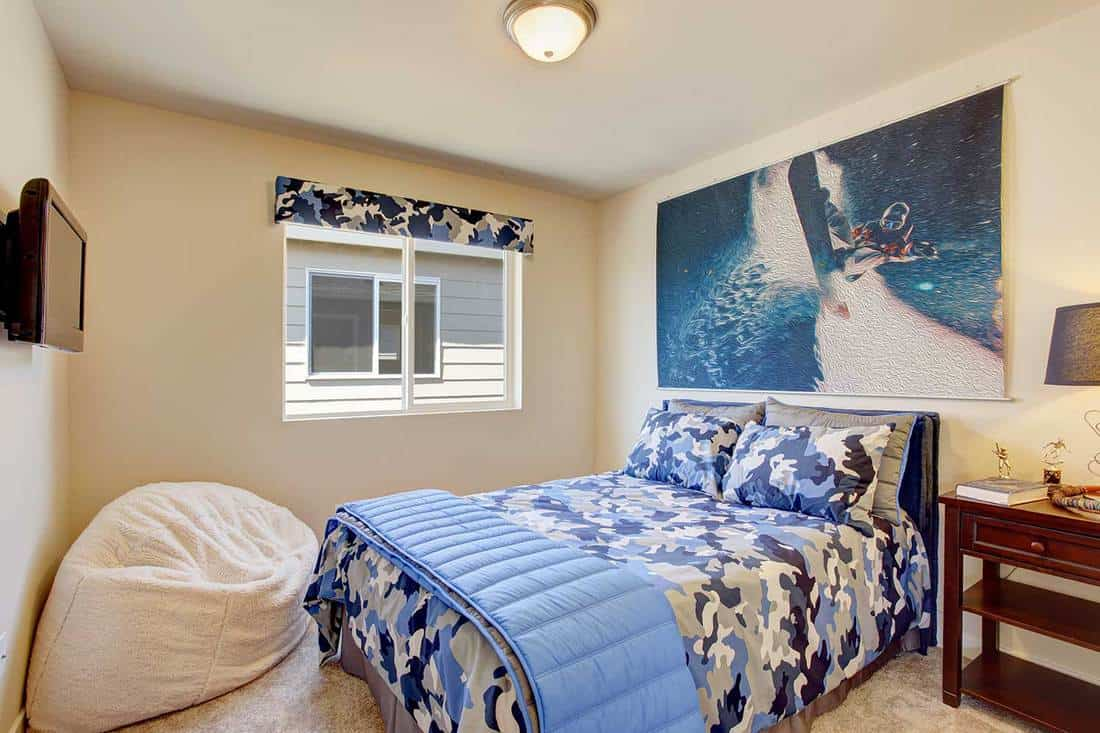 Bright boys room interior with blue bed and tv