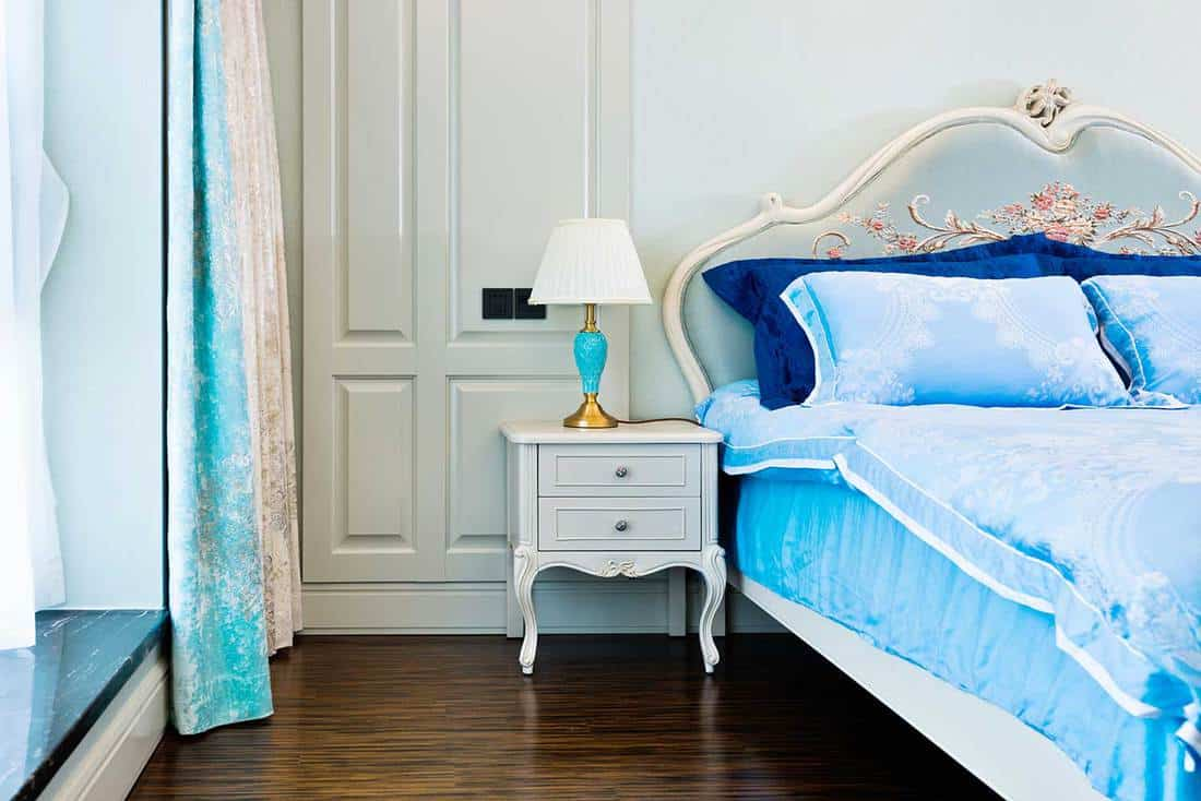 Classic bedroom with blue bed and lamp