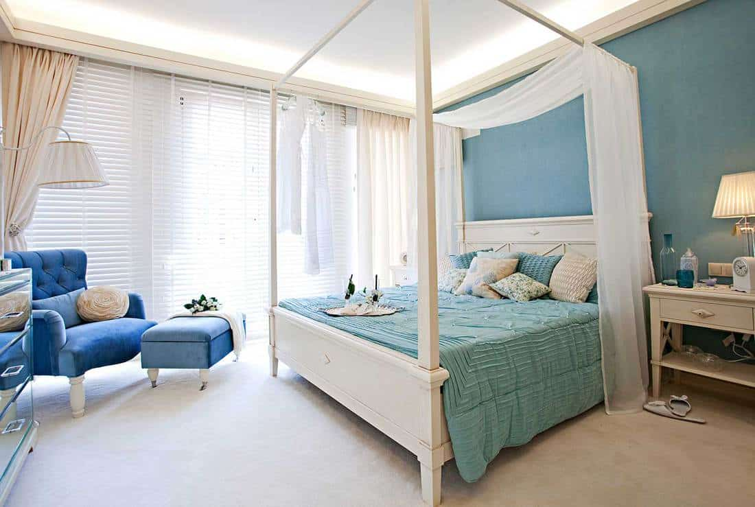 Classic bedroom with teal bed and blue sofa