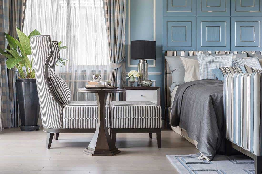 Classic chair with wooden table on wooden floor in blue bedroom