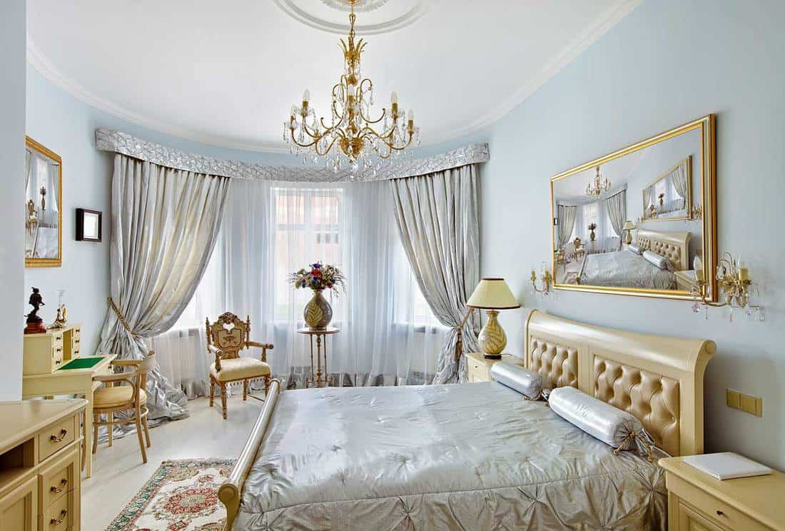 Classic style luxury bedroom interior in blue colors with boudoir and window