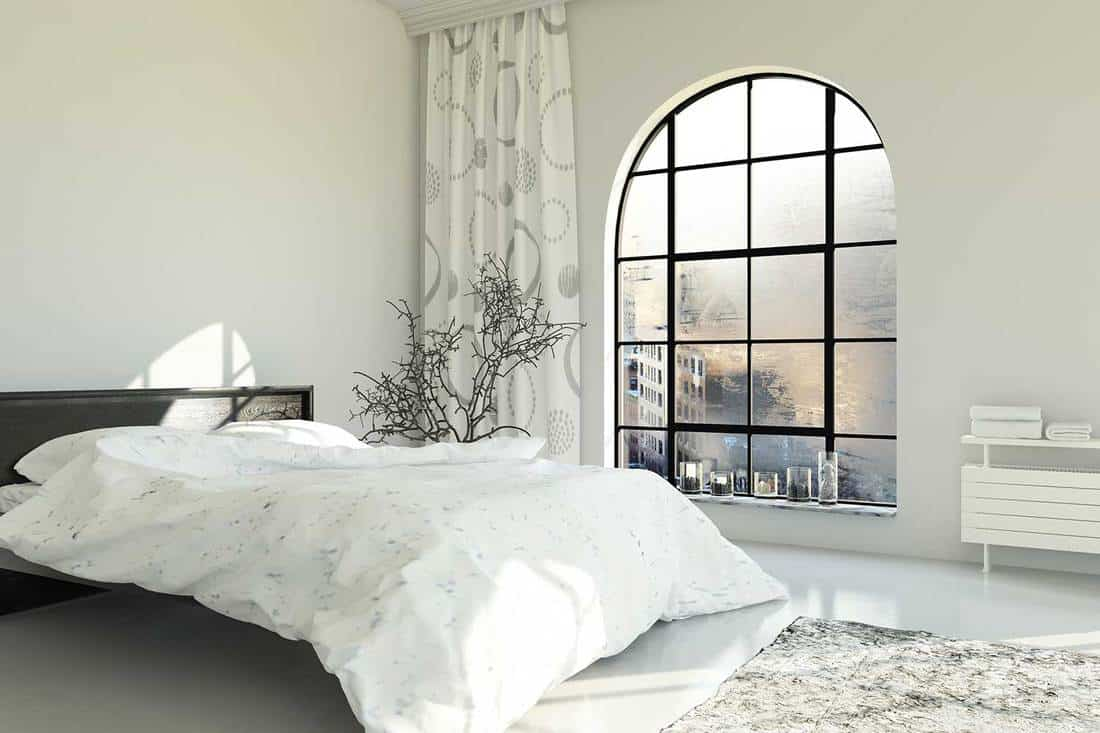 Cozy white bed with city overview window