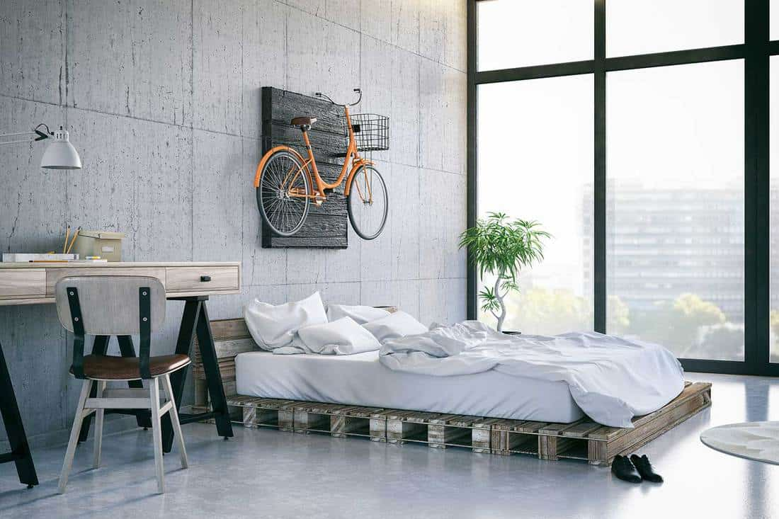 Cozy white bed with orange bike hanging on the wall