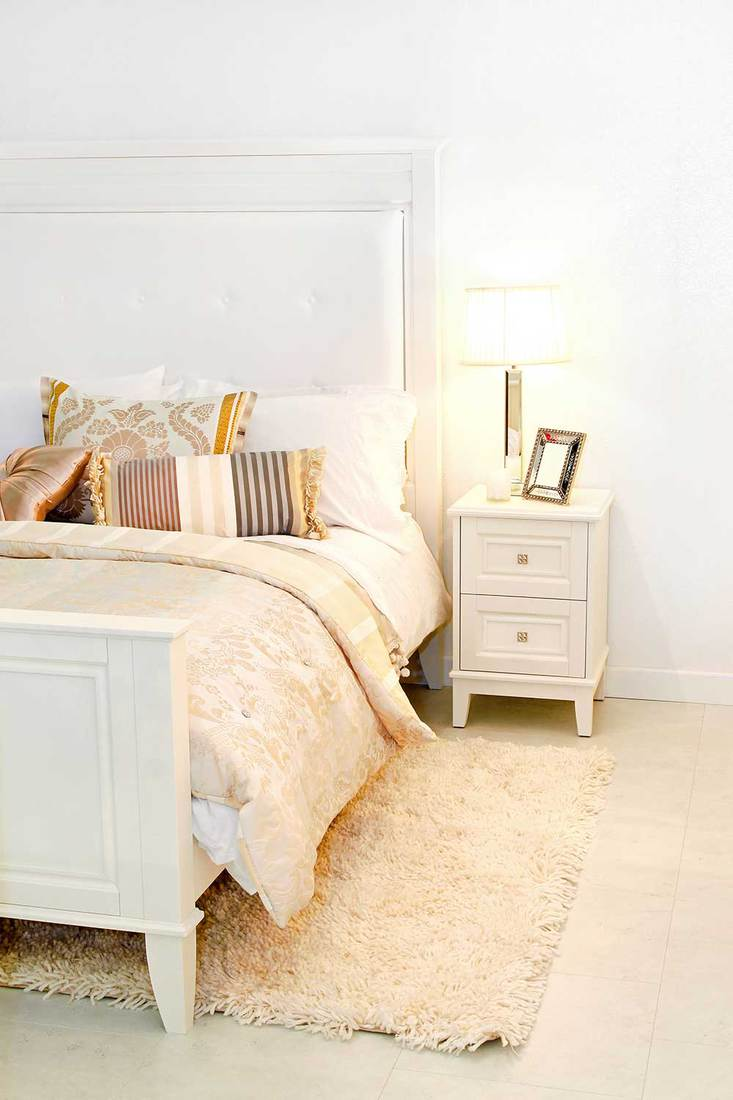 Detail of elegant cozy white bedroom with nightstand