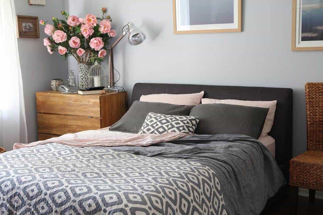 Domestic bedroom with grey, pink pillow case and wooden interior