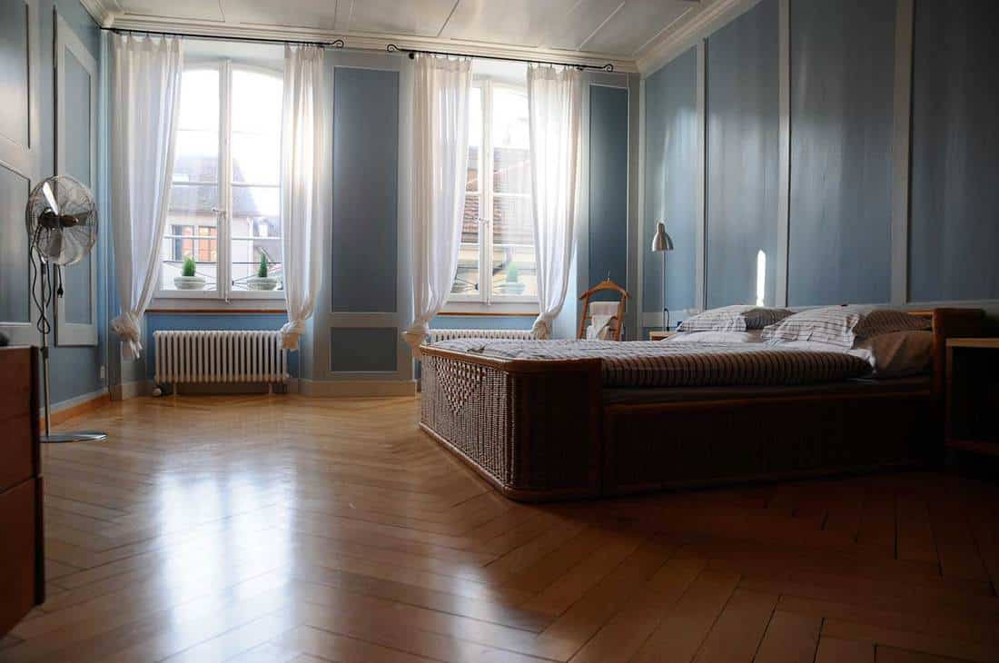 Light blue wall bedroom with wooden bed and parquet flooring