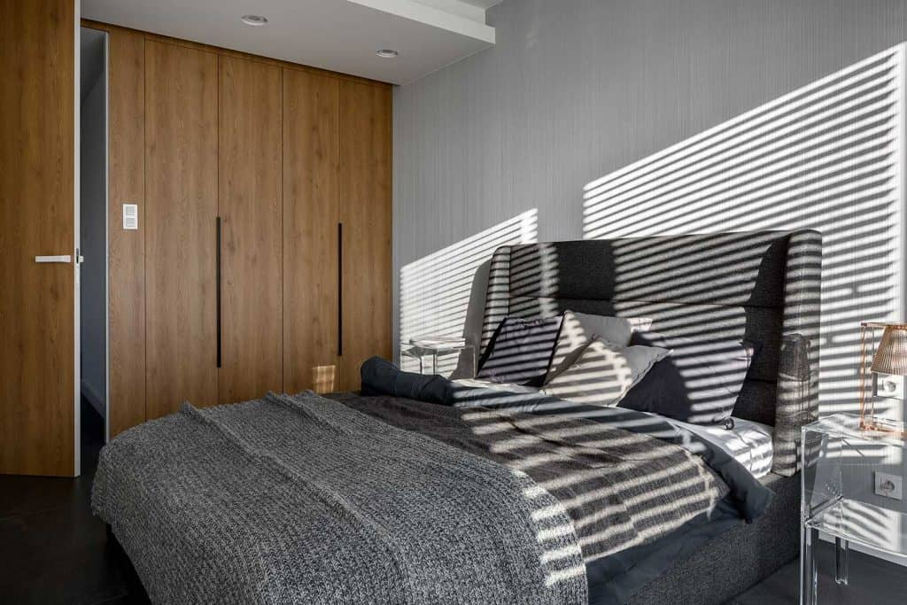 Modern bedroom with grey bed and wardrobe