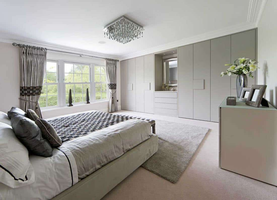 Modern bedroom with patterned bedsheets and grey carpet