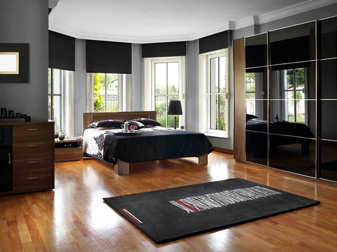 Modern black and white bedroom with parquet flooring