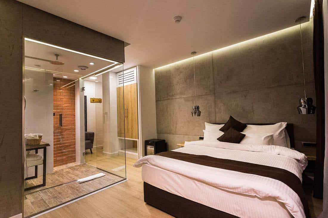 Modern hotel room with transparent glass bathroom