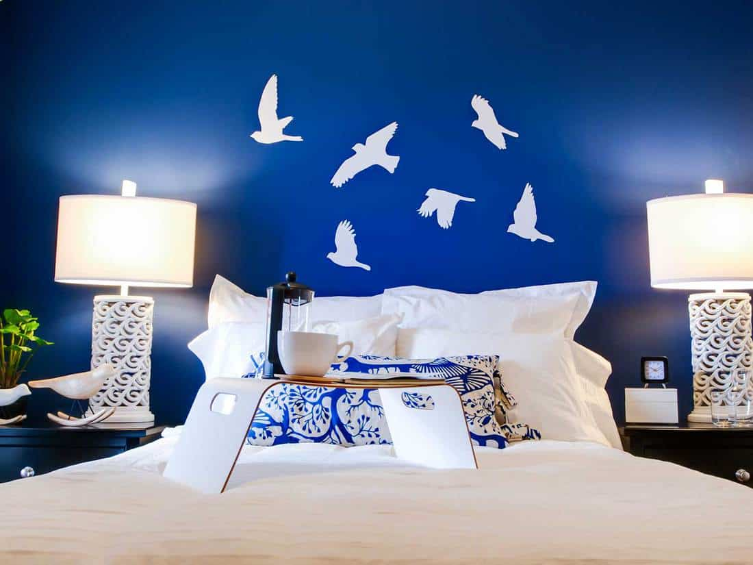 Modern master bedroom with blue wall and white linens