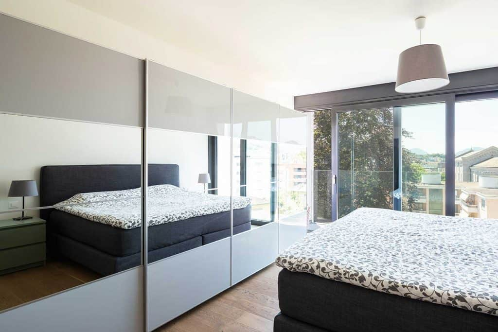 Modern minimalist bedroom with sliding glass wardrobe