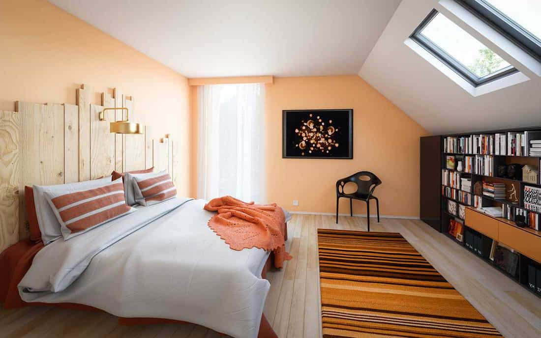 Modern white and orange themed attic bedroom with parquet floor and bookshelf