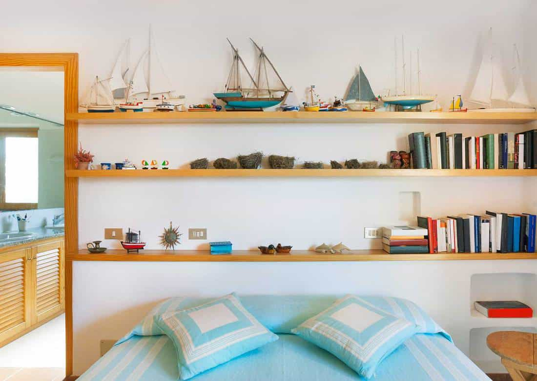 Nautical-themed-bedroom-with-wooden-little-boats-on-the-shelves