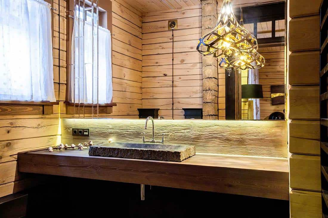 Rustic bathroom with modern interior and stone counter top washbasin