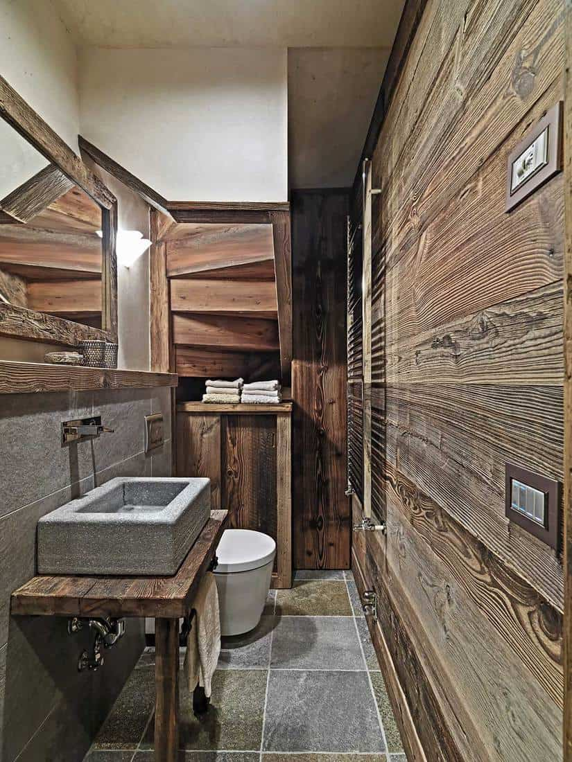Rustic bathroom with wainscoting, stone floor in the foreground and stone counter top washbasin