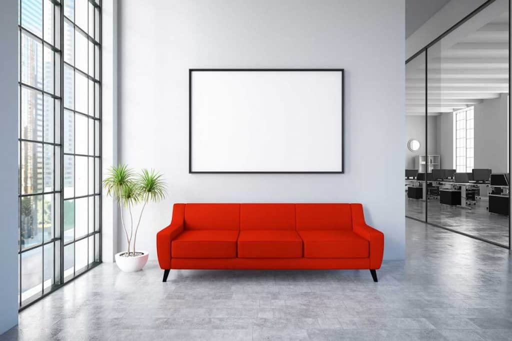 Red couch and blank frame hang on grey wall
