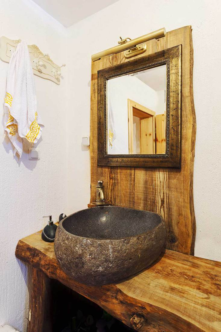 Simple rustic bathroom with stone counter top washbasin