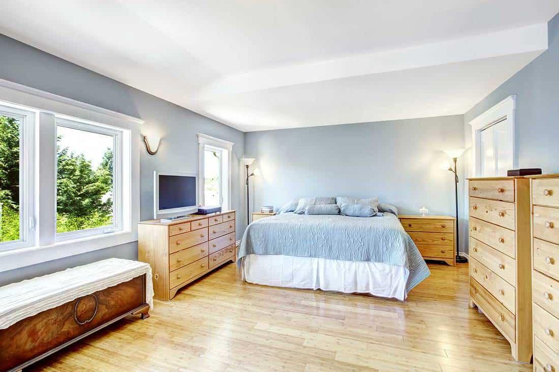 Very bright bedroom in light blue tones with wooden furniture set and hardwood floor