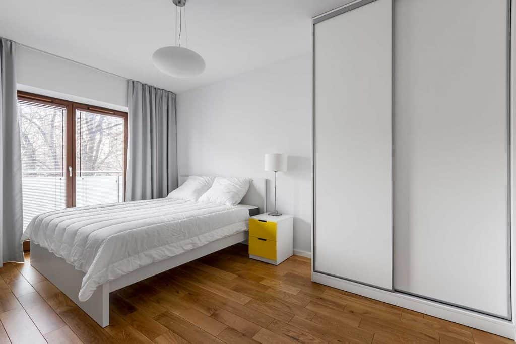 White bedroom with parquet flooring and wardrobe