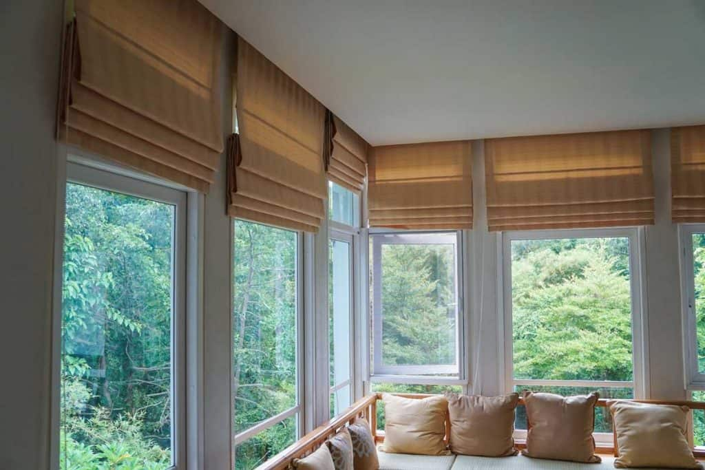 Glass windows with nature view in a modern living room with brown curtains